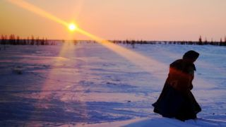 A Nenets woman walks on a snow-covered field in the remote Yamalo-Nenets region of northern Russia on March 8, 2018. / AFP PHOTO / Sergei GAPON