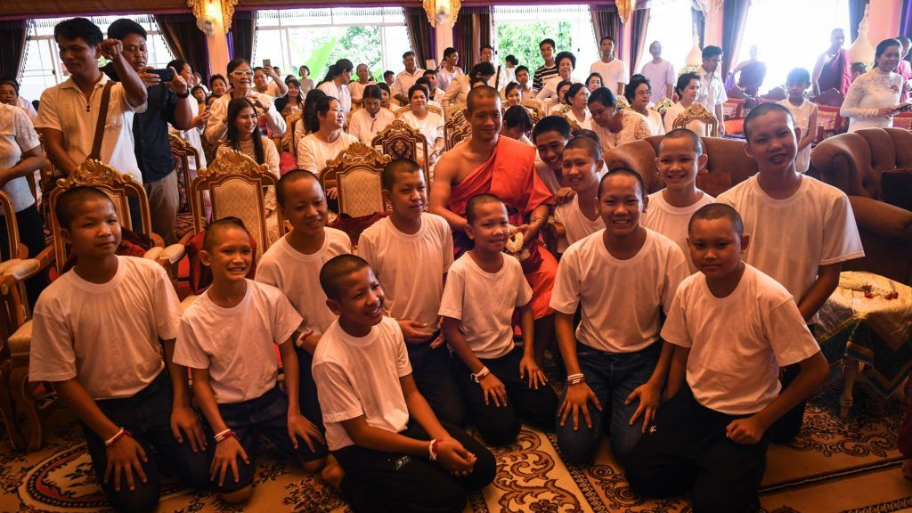 """Thai coach Ekkapol Chantawong (C) and all 12 members of the """"Wild Boars"""" football team pose for a photo together after a ceremony to mark the end of the 11 players' retreat as novice Buddhist monks at the Wat Phra That Doi Tung temple in the Mae Sai district of Chiang Rai province on August 4, 2018. The Thai boys freed from a flooded cave in a rescue bid that gripped the world left the Buddhist monastery 11 days after ordaining as novice monks to honour a diver who died in the mission to save them. / AFP PHOTO / Lillian SUWANRUMPHA"""
