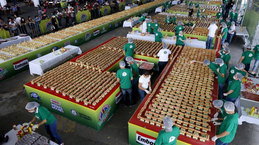 People prepare hundreds of Hot Dogs in an attempt to break the Guinness record of the longest hot dog line in Guadalajara, Jalisco State, on August 12, 2018.  Mexico set a Guinness Record by presenting a row of hot-dogs of 1,417 meters long, the largest in the world. / AFP PHOTO / ULISES RUIZ