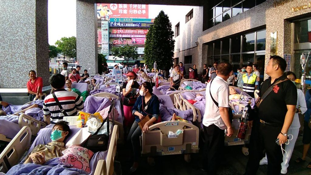 """This photograph by Taiwan agency CNA Photo taken on August 13, 2018 shows bed-ridden patients outside the entrance to a hospital in New Taipei City after being evacuated following a fire on the seventh floor of a hospice. Nine people were killed and 15 injured in a blaze that broke out early on August 13 at the hospice for the terminally ill, near Taiwan's capital Taipei, fire officials said. / AFP PHOTO / CNA PHOTO / CNA PHOTO /  - Taiwan OUT - China OUT - Hong Kong OUT - Macau OUT / -----EDITORS NOTE --- RESTRICTED TO EDITORIAL USE - MANDATORY CREDIT """"AFP PHOTO / CNA PHOTO"""" - NO MARKETING - NO ADVERTISING CAMPAIGNS - DISTRIBUTED AS A SERVICE TO CLIENTS"""