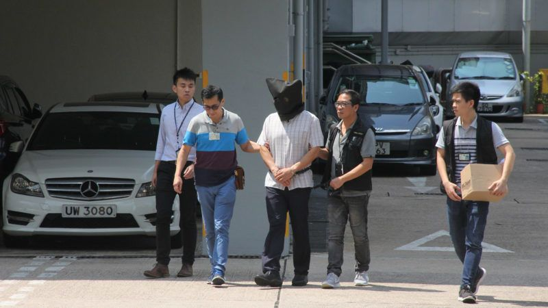 """This handout photograph from Apple Daily taken on September 11, 2017 shows Malaysian national Khaw Kim-sun (C), who is accused of murdering his wife and daughter, being escorted by police at Ma On Shan Police Station in Hong Kong. Khaw Kim-sun, an anaesthetist, gassed his wife and daughter to death using a yoga ball filled with carbon monoxide, a Hong Kong court has heard. Prosecutors told the High Court that Khaw Kim-sun left the inflatable ball in the boot of a car where the gas leaked out and killed them, according to reports from court on August 22, 2018.  / AFP PHOTO / Apple Daily / Handout / Hong Kong OUT - Taiwan OUT - NO Internet / RESTRICTED TO EDITORIAL USE - MANDATORY CREDIT """"AFP PHOTO / APPLE DAILY"""" - NO MARKETING - NO ADVERTISING CAMPAIGNS - DISTRIBUTED AS A SERVICE TO CLIENTS   - NO ARCHIVES  - NO INTERNET"""