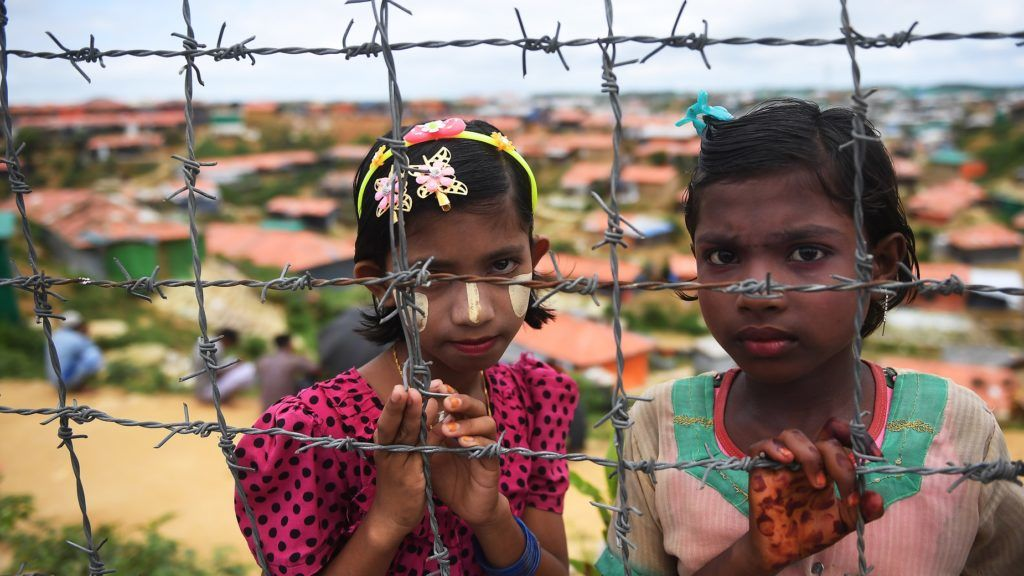"""Rohingya refugees look on as others offer prayer during a ceremony organised to remember the first anniversary of a military crackdown that prompted a massive exodus of people from Myanmar to Bangladesh, at the Kutupalong refugee camp in Ukhia on August 25, 2018.      Tens of thousands of Rohingya refugees staged angry protests for """"justice"""" on August 25 on the first anniversary of a Myanmar military crackdown that sparked a mass exodus to camps in Bangladesh.  / AFP PHOTO / Dibyangshu SARKAR"""