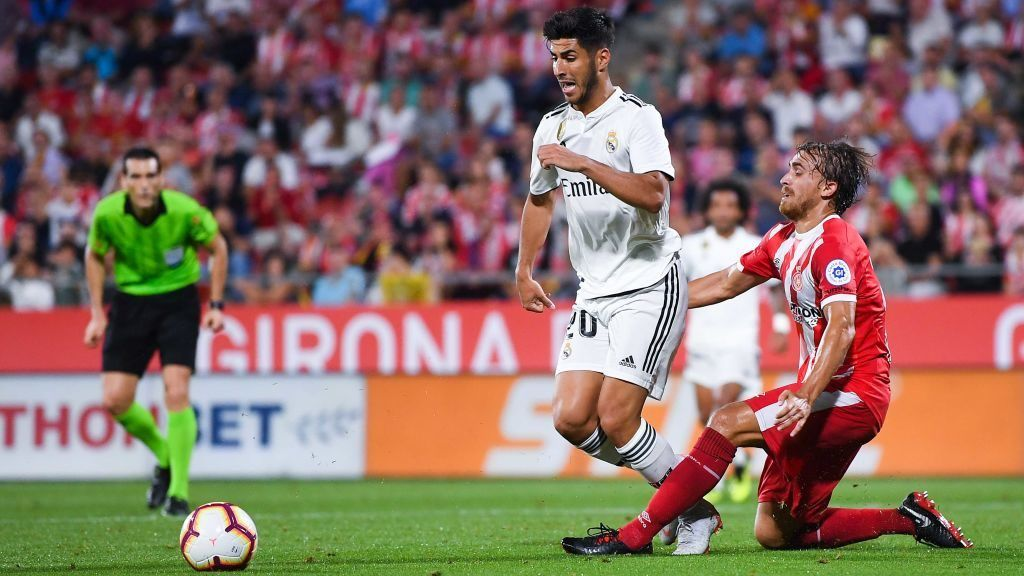 GIRONA, SPAIN - AUGUST 26: Marco Asensio of Real Madrid CF is brought down by Marc Muniesa of Girona FC  during the La Liga match between Girona FC and Real Madrid CF at Montilivi Stadium on August 26, 2018 in Girona, Spain.  (Photo by David Ramos/Getty Images)