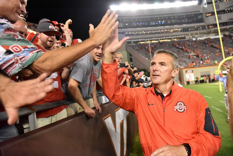 BLACKSBURG, VA - SEPTEMBER 7: Head coach Urban Meyer of the Ohio State Buckeyes shakes hands with the visiting fans following the game against the Virginia Tech Hokies at Lane Stadium on September 7, 2015 in Blacksburg, Virginia. Ohio State defeated Virginia Tech 42-24. (Photo by Michael Shroyer/Getty Images)