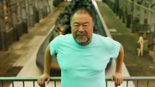 SYDNEY, AUSTRALIA - MARCH 12:  Ai Weiwei poses in front of his work 'Law of the Journey' on March 12, 2018 in Sydney, Australia. The 60m rubber raft installation features over 300 larger than life size figures and is part of the 21st Biennale of Sydney.  (Photo by Don Arnold/WireImage)