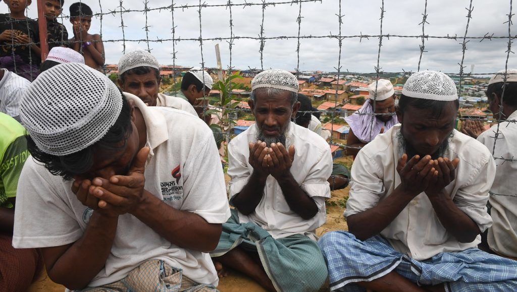 """Rohingya refugees perform prayers as they attend a ceremony organised to remember the first anniversary of a military crackdown that prompted a massive exodus of people from Myanmar to Bangladesh, at the Kutupalong refugee camp in Ukhia on August 25, 2018.   Tens of thousands of Rohingya refugees staged angry protests for """"justice"""" on August 25 on the first anniversary of a Myanmar military crackdown that sparked a mass exodus to camps in Bangladesh.  / AFP PHOTO / Dibyangshu SARKAR"""