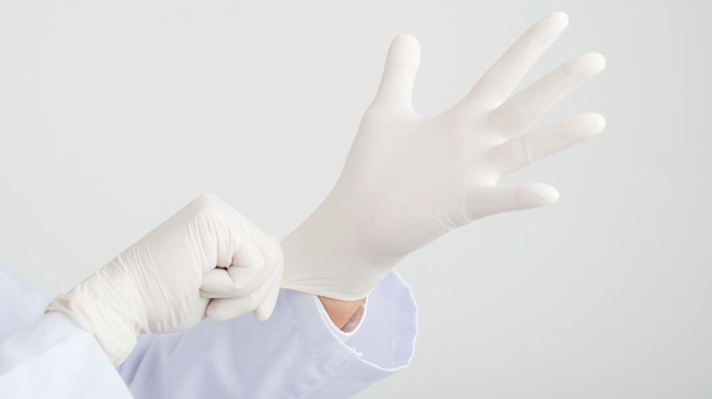 Hands of surgeon wearing rubber gloves before the operation