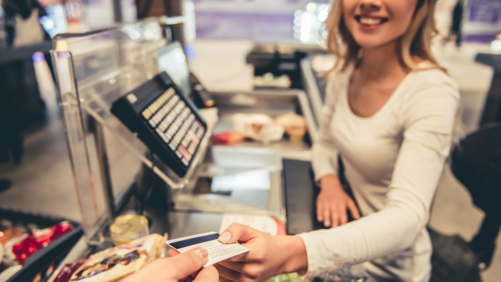 Beautiful young cashier is holding a credit card and smiling while working at the supermarket