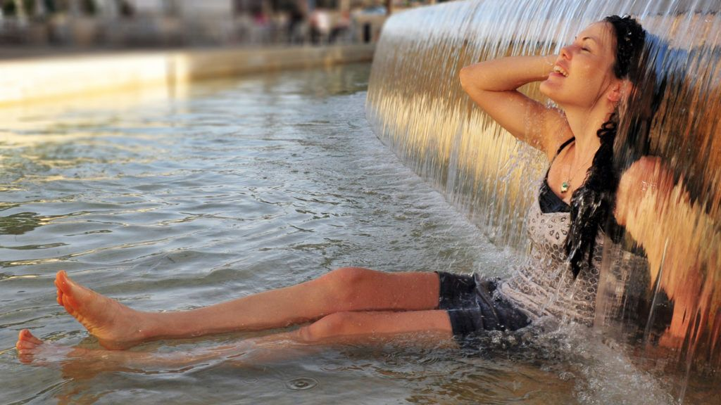 Woman enjoy the cold waters of  fountain  during a heat wave.