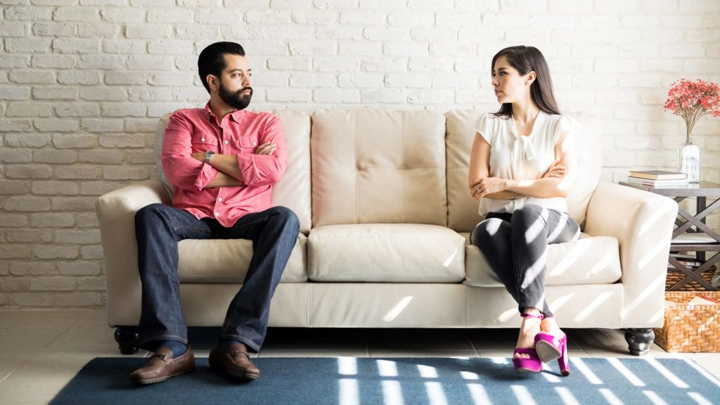 Husband and wife sitting on sofa with their arms crossed and looking at each other after a fight in living room