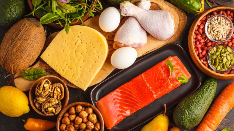 Keto diet concept. Balanced low-carb food background. Vegetables, fish, meat, cheese, nuts on a dark background.