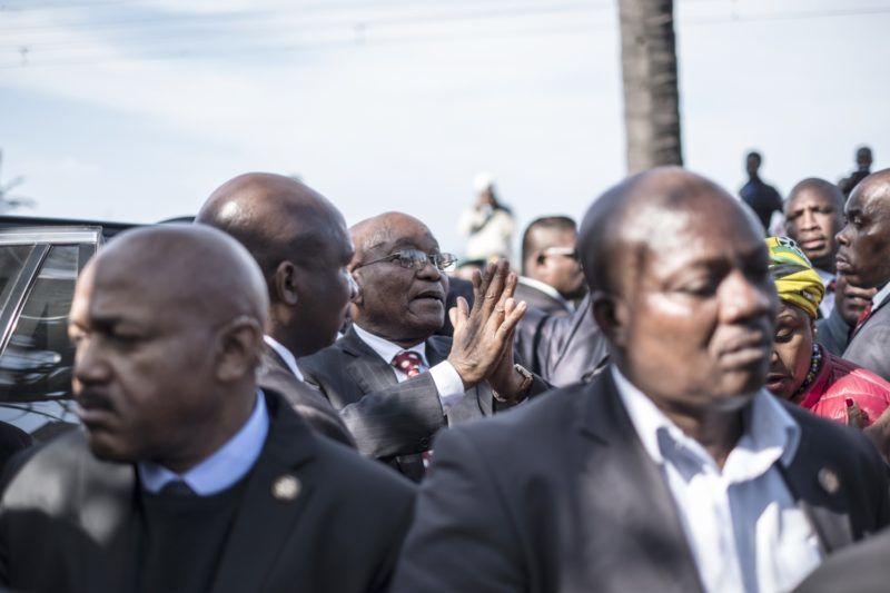 Former South African president Jacob Zuma is seen surrounded by his bodyguards as he leaves a stage where he delivered a speech in Durban, on June 8, 2018 during a rally in his support outside the High Court. South Africa's ex-president Jacob Zuma appeared in court on June 8, 2018 ahead of a corruption trial, raising questions about ballooning legal costs before addressing adoring crowds outside who condemned his prosecution. In front of Durban's stone-fronted High Court, thousands of Zuma supporters sang anti-apartheid struggle songs, flew flags bearing Zuma's face and chanted his name as he was swept into court flanked by tight security.  / AFP PHOTO / MARCO LONGARI