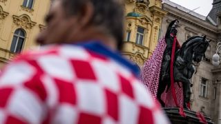 A man dressed in the Croatian national colours walks past the monument of the 19th-century rebel nobleman, Ban Jelacic, covered with Croatian national colours, in downtown Zagreb on July 15, 2018, ahead of the 2018 Russia World Cup final football match between Croatia and France, the first final World Cup match ever in the history of Croatia. / AFP PHOTO / ANDREJ ISAKOVIC