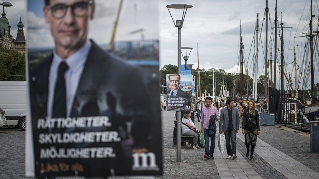 People walk next to an election poster of Ulf Kristersson, leader of the Moderate Party in Sweden on September 1, 2018 in Stockholm.The general elections in Sweden will take place on September 9, 2018. / AFP PHOTO / Jonathan NACKSTRAND
