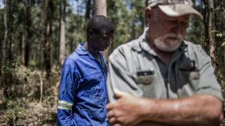 Farm worker Mogoala Justice Ratalele (L) stand near his boss farmer Hans Bergmann (R) after an incident in which he was held at gunpoint for the theft of the chainsaw that he was working with, on November 2, 2017, in Tzaneen, South Africa. A long campaign of violence against the country's farmers, who are largely white, has inflamed political and racial tensions nearly a quarter-of-a-century after the fall of apartheid.  / AFP PHOTO / GULSHAN KHAN