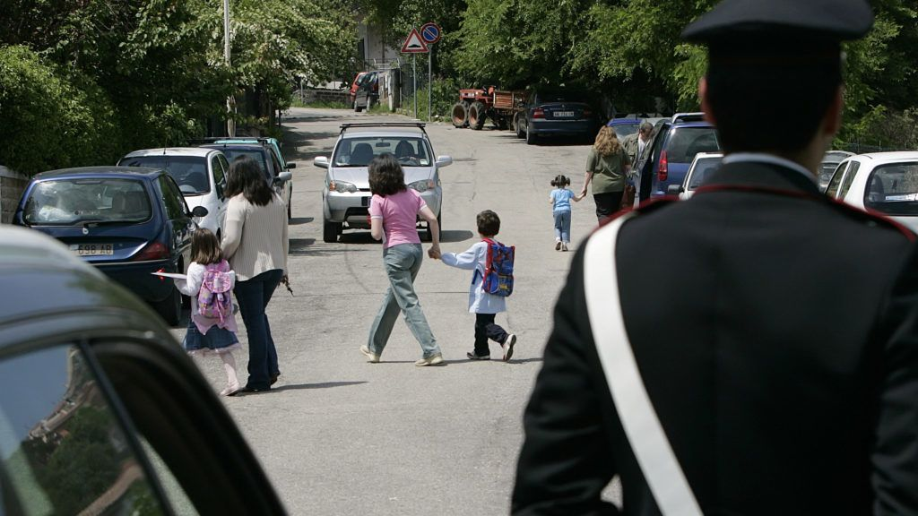 """An Italian Carabiniere military policeman patrols the entrance of the """"Olga Rovere"""" nursery school at Rignano Flaminio, 40km (25 miles) north of Rome, as mothers leaves with theirs children May 11, 2007. Rignano Flaminio has not been the same since police burst into its model nursery school seven months ago seeking evidence of child abuse. The arrest last month of three teachers horrified parents and has sparked lurid headlines about the school of horrors.   REUTERS/Max Rossi  (ITALY)"""