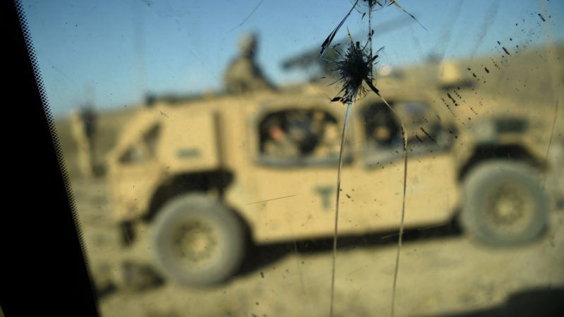 """In this photo taken on July 7, 2018, US Army soldiers from NATO are seen through a cracked window of an armed vehicle in a checkpoint during a patrol against Islamic State militants at the Deh Bala district in the eastern province of Nangarhar Province.  A US soldier was killed and two others wounded in an """"apparent insider attack"""" in southern Afghanistan on July 8, NATO said, the first such killing in nearly a year. / AFP PHOTO / WAKIL KOHSAR"""