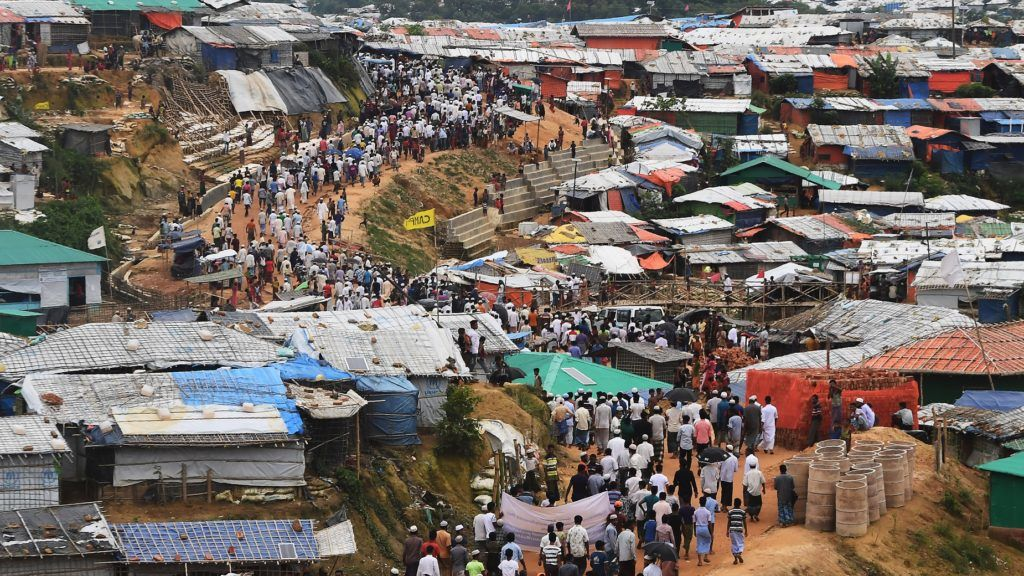 """Rohingya refugees walk in a protest march after attending a ceremony to remember the first anniversary of a military crackdown that prompted a massive exodus of people from Myanmar to Bangladesh, at the Kutupalong refugee camp in Ukhia on August 25, 2018. Tens of thousands of Rohingya refugees staged angry protests for """"justice"""" on August 25 on the first anniversary of a Myanmar military crackdown that sparked a mass exodus to camps in Bangladesh.  / AFP PHOTO / Dibyangshu SARKAR"""