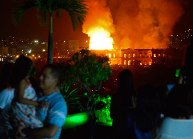 People watch as a massive fire engulfs the National Museum in Rio de Janeiro, one of Brazil's oldest, on September 2, 2018.  The cause of the fire was not yet known, according to local media. / AFP PHOTO / STR