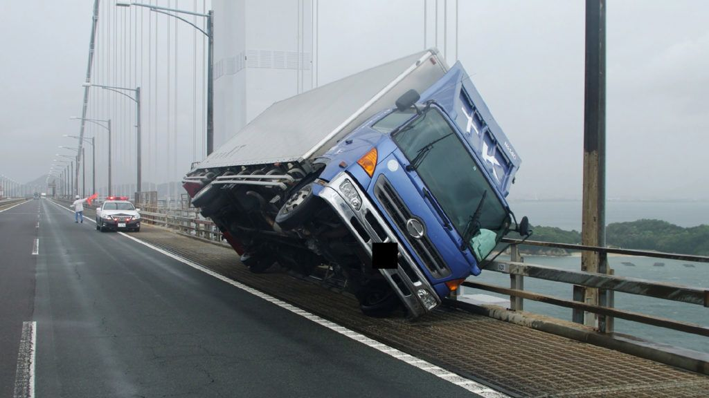 """This handout photo released by the Kagawa Prefectural Police on September 4, 2018 and received via Jiji Press shows a truck sitting at an angle after being blown over by strong winds caused by Typhoon Jebi on the Seto Ohashi bridge in Sakade, Kagawa prefecture on Japan's Shikoku island. The strongest typhoon to hit Japan in 25 years made landfall on September 4, the country's weather agency said, bringing violent winds and heavy rainfall that prompted evacuation warnings. / AFP PHOTO / JIJI PRESS AND Kagawa Prefectural Police / JIJI PRESS /  - Japan OUT / EDITOR'S NOTE: Car's licence plate was digitally blocked by Kagawa prefectural police -----EDITORS NOTE --- RESTRICTED TO EDITORIAL USE - MANDATORY CREDIT """"AFP PHOTO / Kagawa prefectural police """" - NO MARKETING - NO ADVERTISING CAMPAIGNS - DISTRIBUTED AS A SERVICE TO CLIENTS /"""