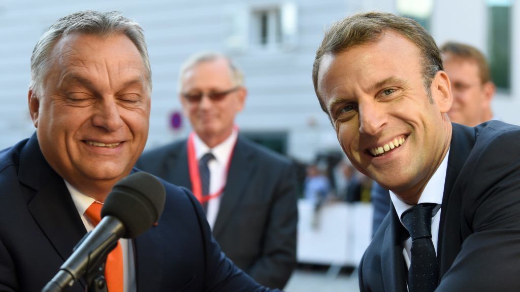 Hungary's Prime Minister Viktor Orban (L) and France's President Emmanuel Macron share a smile as they arrive at the Mozarteum University to attend a plenary session part of the EU Informal Summit of Heads of State or Government in Salzburg, Austria, on September 20, 2018. / AFP PHOTO / Christof STACHE