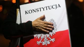 A man holds a banner-shield marked  'Constitution' during a protest at the Main Square against government plans for sweeping changes to Polands judicial system.  Krakow, Poland on 22 September, 2018. The European Network of Councils for the Judiciary (ENCJ) has suspended the Polish council membership and the European Commission decided this week to take Poland to the top European Union court over the controversial court reforms.  (Photo by Beata Zawrzel/NurPhoto)