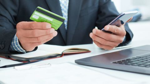 Business, technology, cash free and internet people concept - male hands holding smart phone and credit card at office.