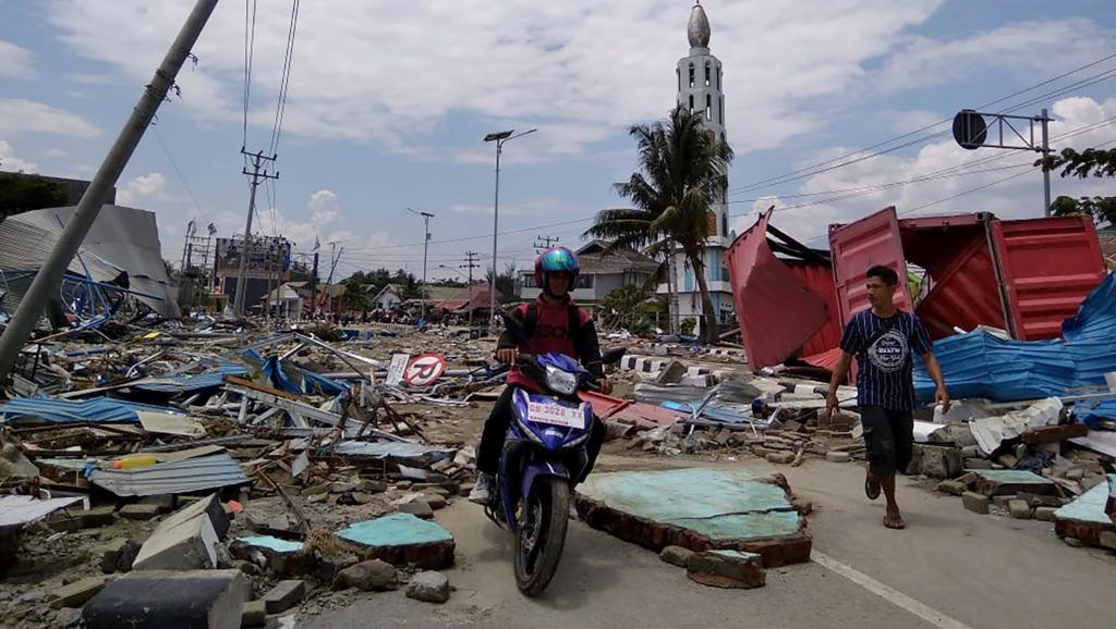 Residents make their way along a street full of debris after an earthquake and tsunami hit Palu, on Sulawesi island on September 29, 2018. Rescuers scrambled to reach tsunami-hit central Indonesia and assess the damage after a strong quake brought down several buildings and sent locals fleeing their homes for higher ground. / AFP PHOTO / MUHAMMAD RIFKI