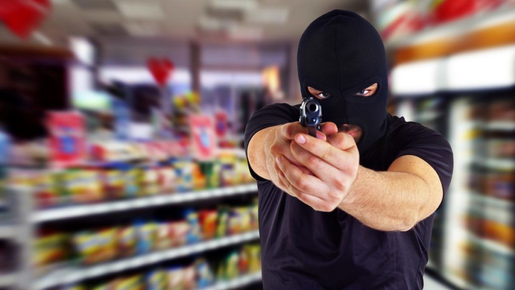 Man in a mask with a gun in the supermarket
