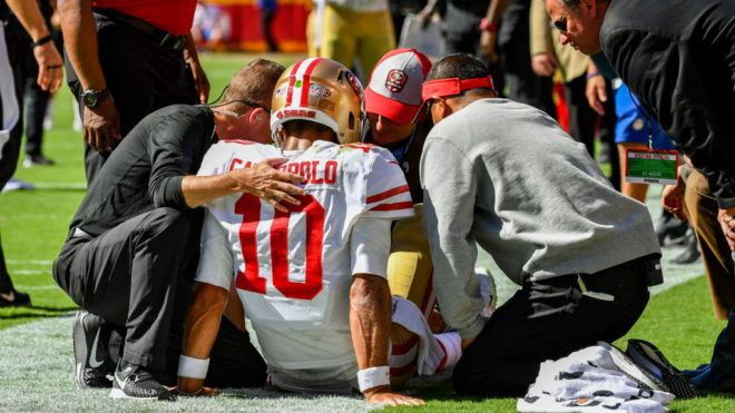 KANSAS CITY, MO - SEPTEMBER 23: Head coach Kyle Shanahan of the San Francisco 49ers and the team training staff examine quarterback Jimmy Garoppolo #10 on the sideline after being hurt on a play during the fourth quarter of the game against the Kansas City Chiefs at Arrowhead Stadium on September 23rd, 2018 in Kansas City, Missouri. (Photo by Peter Aiken/Getty Images)