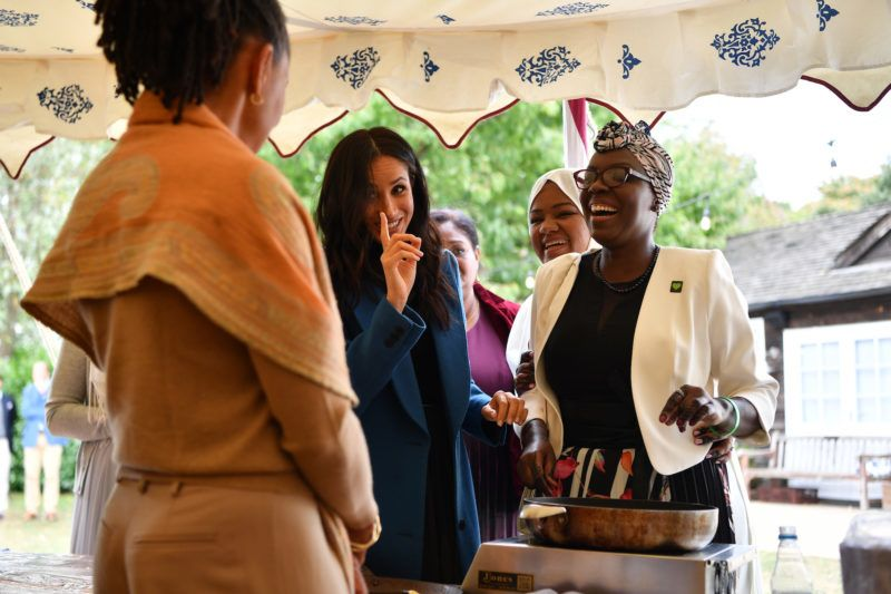 LONDON, ENGLAND - SEPTEMBER 20: Meghan, Duchess of Sussex (C) jokes with her mother Doria Ragland (L) at an event to mark the launch of a cookbook with recipes from a group of women affected by the Grenfell Tower fire at Kensington Palace on September 20, 2018 in London, England. (Photo by Ben Stansall - WPA Pool/Getty Images)