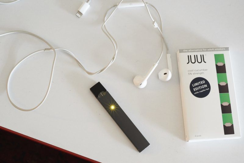 A Juul Labs Inc. e-cigarette and flavored pod are arranged for a photograph in the Brooklyn Borough of New York, U.S., on Sunday July 8, 2018. Juul Labs, the maker of the popular e-cigarette brand that has recently come under fire from health officials over its popularity with young adults, plans to introduce a line of lower-nicotine pods. The company will begin to sell pods with a 3-percent nicotine concentration in its mint and Virginia tobacco flavors later this year, according to a statement Thursday. Photographer: Gabby Jones/Bloomberg via Getty Images