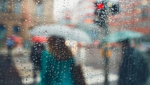 Gloomy day in the city. People in heavy rain. Selective focus on the raindrops. Prague, Czech Republic