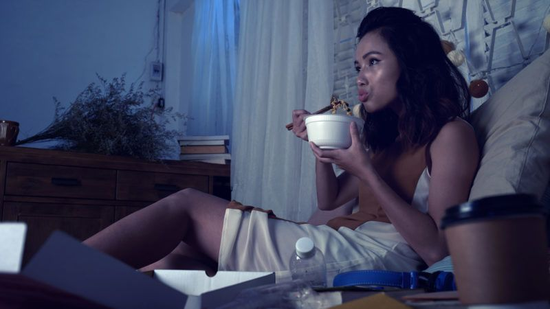 Pretty woman eating ramen soup and watching tv series late at night