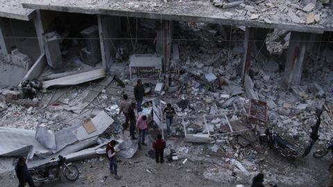 A picture taken on March 22, 2018 shows Syrian civilians gathering at a scene of destruction following an air strike in the rebel-held town of Harem in the northwestern Idlib province. (Photo by Aaref WATAD / AFP)
