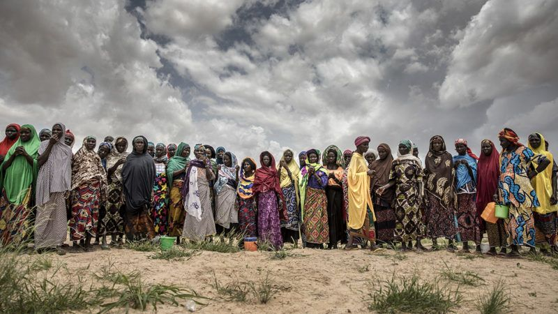 A group of woman working at sorghum crops wait upon the arrival of a United Nations convoy near the village of Sabon Machi, Maradi region, Niger on August 16, 2018. Several UN Agencies (FAO, WFP and IFAP) along with the Government of Niger and other partners visited the agropastoral Maradi region of Niger to understand the context and local priorities, espcially the needs of women and other vulnerable groups in the area. In Niger, as in many other parts of the Sahel, climate shocks have resulted in recurring droughts with devastating impacts on the region's already vulnerable populations. (Photo by Luis TATO / AFP)