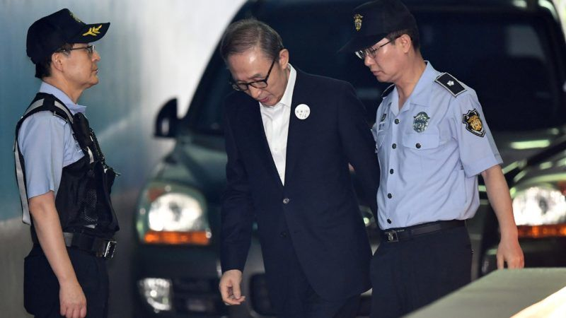 Former South Korean president Lee Myung-bak (C) arrives at a court to attend his trial in Seoul on September 6, 2018. Prosecutors demanded 20 years in prison for former South Korean president Lee Myung-bak for corruption,  the last of the country's four living ex-leaders to be embroiled in a criminal inquiry. / AFP PHOTO / Jung Yeon-je