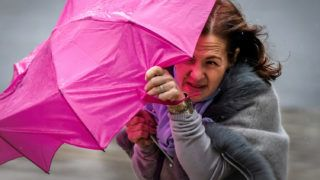 A woman shelters under an umbrella from the wind and rain in Moscow on September 28, 2018. (Photo by Yuri KADOBNOV / AFP)