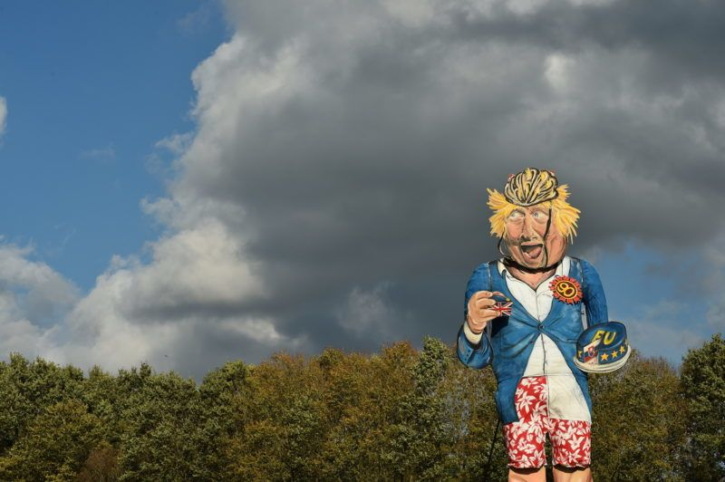 The Edenbridge Bonfire Society's 2018 'Celebrity Guy', former British foreign secretary Boris Johnson, created by artist Andrea Deans, is seen during the unveiling in Edenbridge, Southern England on October 31, 2018. - The giant effigy of Boris Johnson, depicted eating a piece of EU-themed cake wearing his trademark boarding shorts and buses at his feet bearing the controversial 350 million-pound Brexit campaign claim, will be burned at the Edenbridge Bonfire Society's annual bonfire night celebrations on November 3, 2018. (Photo by Glyn KIRK / AFP) / RESTRICTED TO EDITORIAL USE - MANDATORY MENTION OF THE ARTIST UPON PUBLICATION - TO ILLUSTRATE THE EVENT AS SPECIFIED IN THE CAPTION