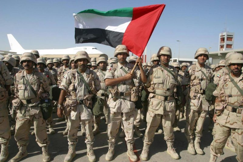 A contingent force from the United Arab Emirates holding their national flag, stand at ease on the tarmac of Kuwait International Airport upon their arrival here 23 February 2003. They are part of the peninsula shield forces which are expected to come to Kuwait in a few days. Kuwait has placed two of its army brigades along the northern borders with Iraq as a preventive major to block any aggression from its neighboring country. AFP PHOTO/Yasser AL-ZAYYAT (Photo by YASSER AL-ZAYYAT / AFP)