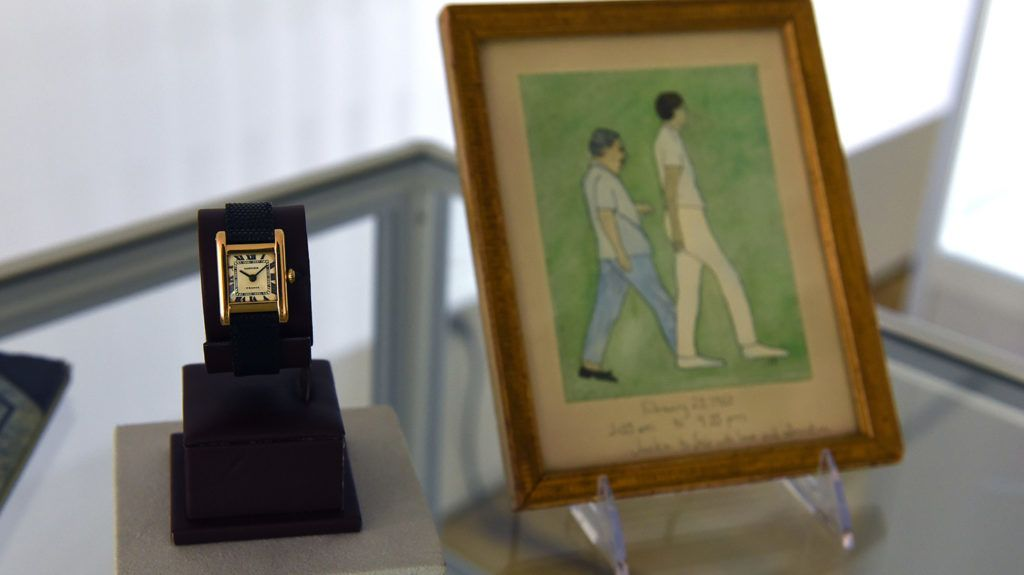 """A Signed Cartier, Tank Model,  Manufactured in 1962 belonging to Jacqueline Kennedy Onassis dubbed the """"The Jacqueline Kennedy Onassis Cartier Tank"""" and a Original Painting by Jacqueline Kennedy Onassis  are displayed at Christie's in New York on June 20, 2017, a day before the Rare Watches and American Icons New York sale. (Photo by TIMOTHY A. CLARY / AFP)"""