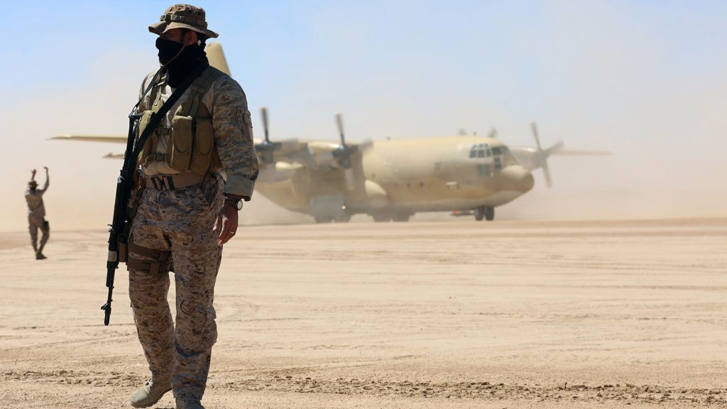 Saudi soldiers stand guard as a Saudi air force cargo plane, carrying aid, lands at an airfield in Yemen's central province of Marib, on February 8, 2018. (Photo by ABDULLAH AL-QADRY / AFP)