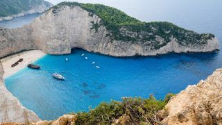 """05.10.2018, Greece, Zakynthos: View from the steep coast into the Navagio bay on the Greek island of Zakynthos in the Ionian Sea. The wreck of the coaster motor ship """"Panagiotis"""" can be seen here. In October 1980, the smuggler ship stranded here when it was pursued by the Coast Guard and suffered a machine failure. Photo: Jens Kalaene / dpa-Zentralbild / ZB 