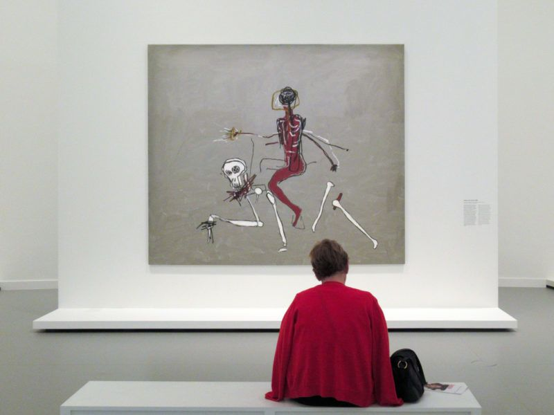 """04 October 2018, France, Paris: A visitor in front of the picture """"Riding with Death"""" by Jean-Michel Basquiat. Photo: Sabine Glaubitz/dpa"""