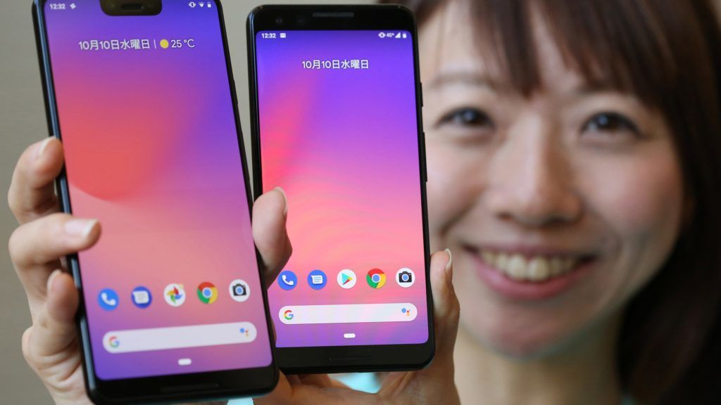 """A woman poses for a photographer with new smartphones """"Google Pixel 3(L)""""and """"Google Pixel 3 XL""""in Shibuya Ward, Tokyo on October 10, 2018.In Japan, the smartphones will be released on November 1.( The Yomiuri Shimbun )"""