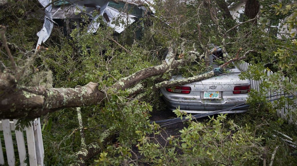 PANAMA CITY, FL - OCTOBER 10: A tree lays on a home and car after hurricane Michael passed through the area on October 10, 2018 in Panama City, Florida. The hurricane hit the Florida Panhandle as a category 4 storm.   Joe Raedle/Getty Images/AFP