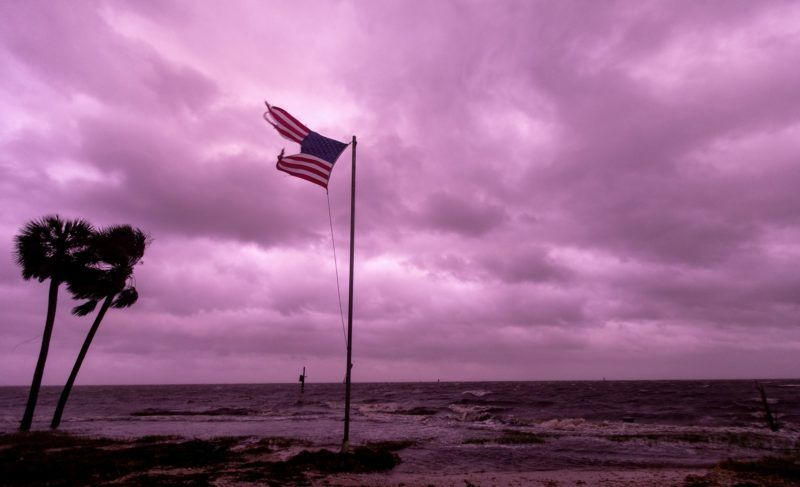 CRAWFORDVILLE - OCTOBER 10: An American flag battered by Hurricane Michael continues to fly in the in the rose colored light of sunset at Shell Point Beach on October 10, 2018 in Crawfordville, Florida.The hurricane hit the Florida Panhandle as a category 4 storm.   Mark Wallheiser/Getty Images/AFP
