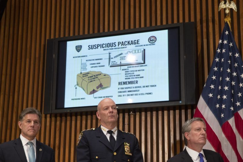 NEW YORK, NY - OCTOBER 25: A monitor displays information about suspicious packages as NYPD Chief of Department Terence Monahan (C) and New York City Mayor Bill de Blasio (R) look on during a press conference regarding the recent package bombings, at NYPD headquarters, October 25, 2018 in New York City.   Drew Angerer/Getty Images/AFP