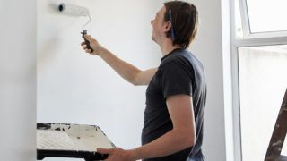 [England] A painter and decorator using a paint roller and holding a paint tray, decorating a room.