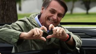 Jair Bolsonaro, far-right lawmaker and presidential candidate for the Social Liberal Party (PSL), gestures to supporters during the second round of the presidential elections, in Rio de Janeiro, Brazil on October 28, 2018. - Brazilians will choose their president today during the second round of the national elections between the far-right firebrand Jair Bolsonaro and leftist Fernando Haddad (Photo by MAURO PIMENTEL / AFP)